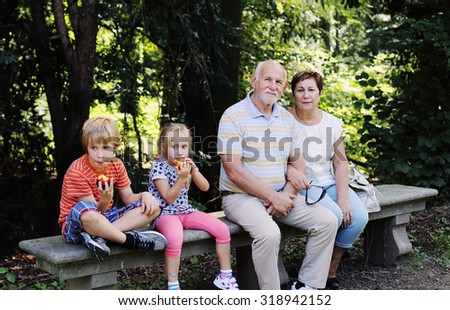 Grandparents With Grandchildren walking together in the park - stock photo