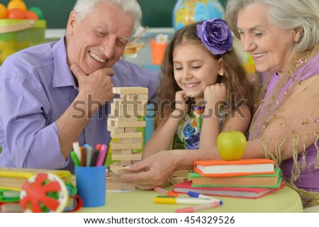 Grandparents with granddaughter playing together - stock photo