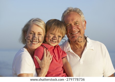 Grandparents With Grandson Enjoying Beach Holiday - stock photo