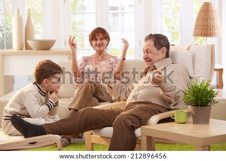 Grandparents with grandson sitting in living room at home having fun together. - stock photo