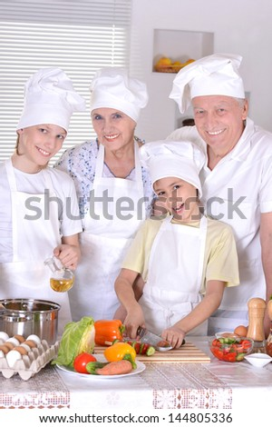 grandparents with two boys are preparing dinner for the family - stock photo