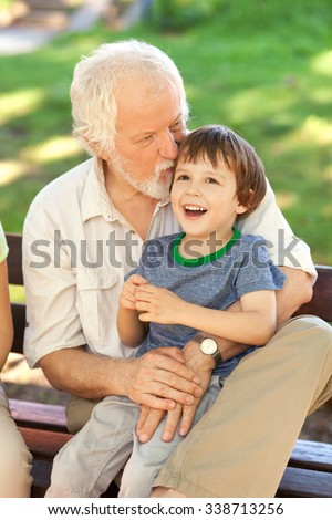 Grandson and grandfather having fun on the park bench, shallow depth of field - stock photo
