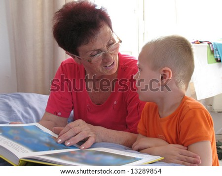 grandson and grandmother read a book - stock photo