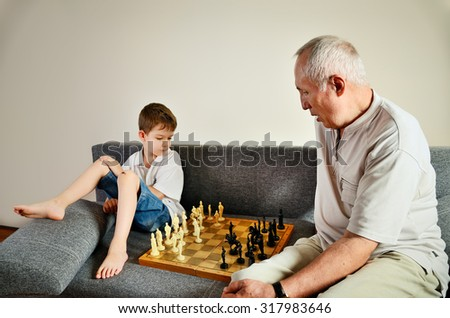grandson and grandpa playing chess horizontal - stock photo