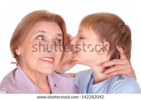 grandson shares the secret with his grandmother on a white background - stock photo