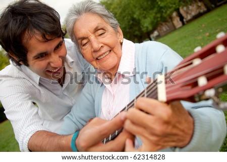 Grandson teaching her grandma how to play the guitar - stock photo