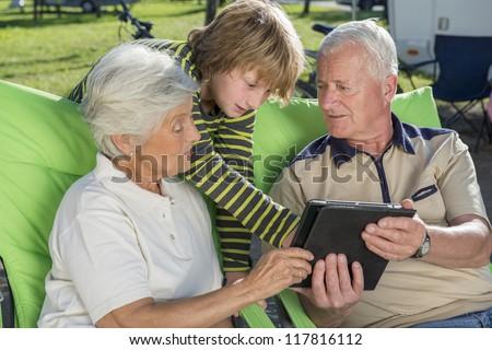 Grandson teaching his grandparents using digital tablet outdoors - stock photo