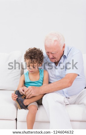 Grandson tying his shoelaces with his grandfather sitting on the sofa