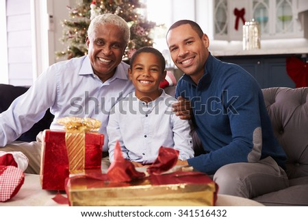 Grandson With Grandfather And Father Opening Christmas Gifts - stock photo