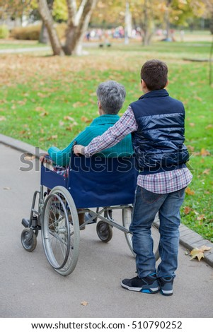 grandson with grandmother sitting in wheel chair at the park