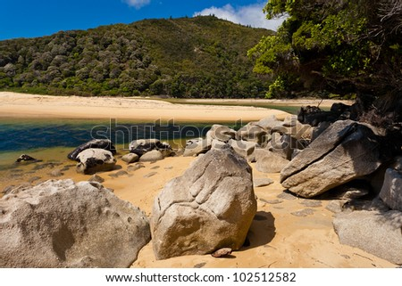 Granite boulders and sandy beach in Abel Tasman National Park, South Island, New Zealand - stock photo