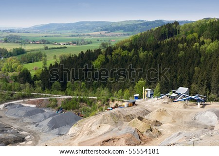 Granite quarry mining in the background crane with a digger - stock photo