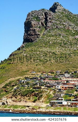 Granite rock promontory above the village at False Bay, seen a boat on the way to Seal Island, Cape Town, South Africa - stock photo