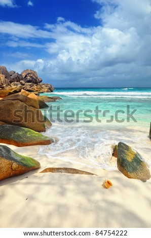 Granite rocky beaches on Seychelles islands, La Digue. Big orange shell in the surf - stock photo