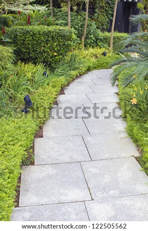Granite Stone Square Pavers Garden Path with Trees Shrubs and Plants - stock photo