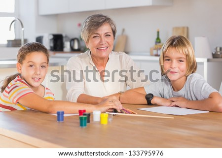 Granny and her grandchildren looking at camera with smile in kitchen - stock photo