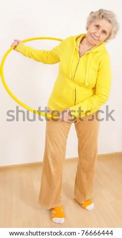 granny doing gymnastic with hula-hoop - stock photo