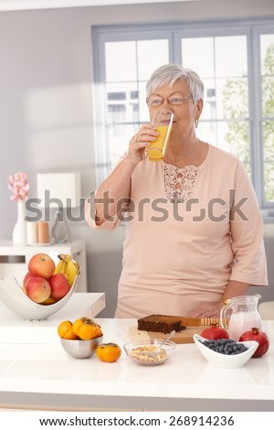 Granny drinking orange juice in the morning at home while preparing healthy breakfast. - stock photo