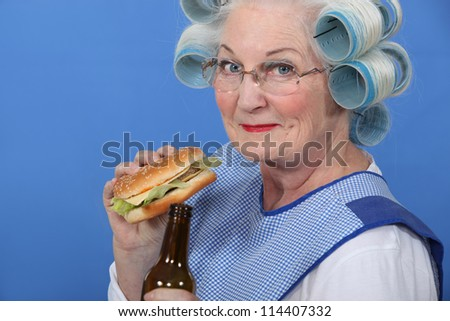 Granny eating a burger and drinking a beer - stock photo