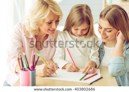 Granny, her daughter and granddaughter are drawing and smiling while sitting at home - stock photo