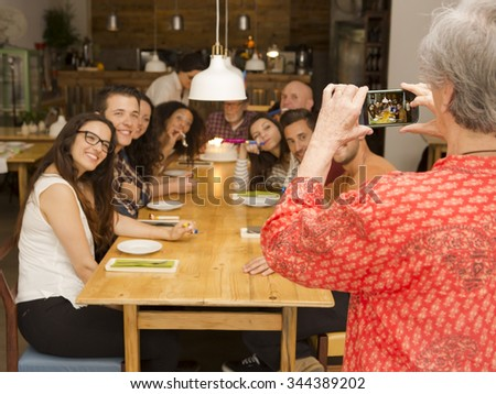 Granny taking a picture of all family celebrating the birthday grandfather