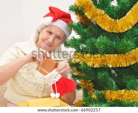 Granny with christmas stocking sitting near christmas tree