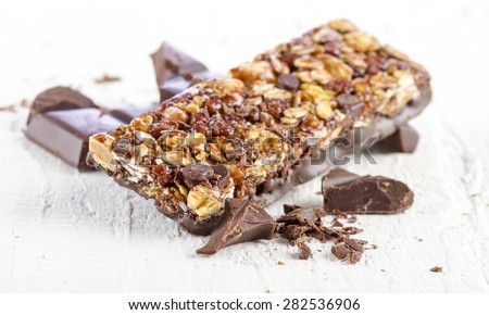 Granola bar with chocolate on white wooden background - stock photo