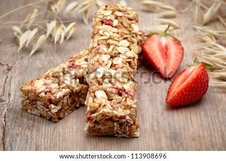 Granola bar with strawberries on wooden background - stock photo