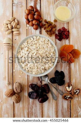 Granola bars ingredients on wood background, top view