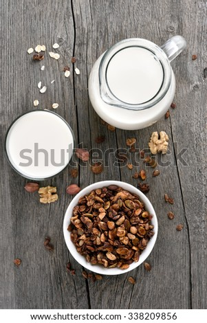 Granola cereal and milk on wooden background, top view - stock photo