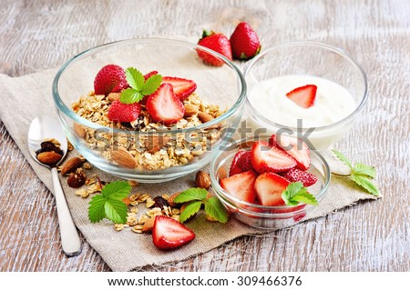 Granola cereal with fresh strawberries, raisins, almonds, and yogurt, muesli for healthy breakfast, morning meal, selective focus - stock photo