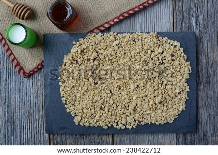 Granola, Honey and Milk with Gray Slate on Dark Wood Background - stock photo