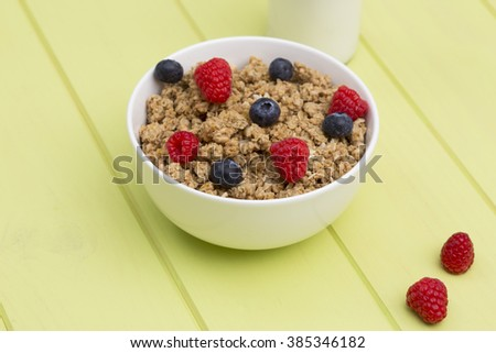 Granola in a bowl with milk, raspberries and blueberries on a wooden table, muesli