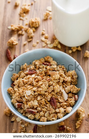 granola in bowl in brown background and bottle of milk - stock photo