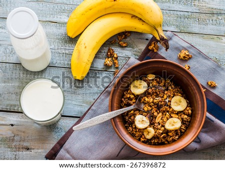 granola with bananas, nuts, figs and honey, milk, healthy breakfast on a gray background - stock photo