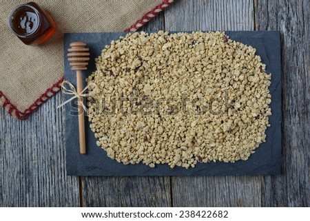 Granola with Burlap and Honey Covering Dark Grey Slate on Dark Wood Background - stock photo