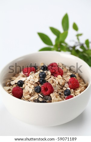 Granola with fresh organic raspberries and blueberries. Shallow DOF - stock photo