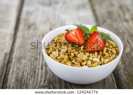 Granola with strawberry on a wooden table. Healthy eating for breakfast.
