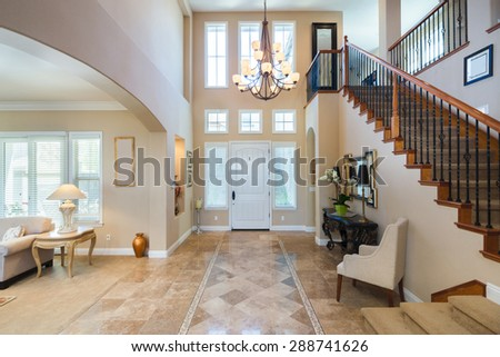 Grant Interior with staircase in large private home with granite floor and large chandelier with adjacent living room. - stock photo