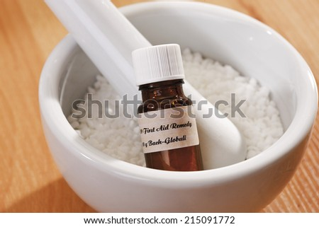 Granulate and bottle with Homeopathic remedy in mortar - stock photo