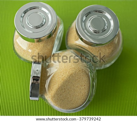 Granulated garlic in transparent jars on a green background - stock photo