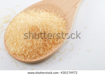 Granulated sugar In a wooden spoon on a white background - stock photo