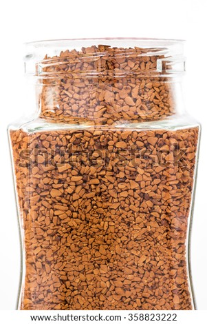 Granules of instant coffee in a glass bottle isolated on white background - stock photo