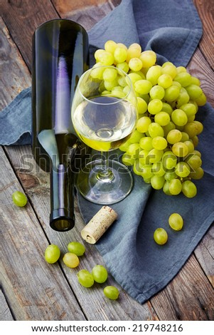 Grape, a bottle and glass of white wine with grape on wooden table