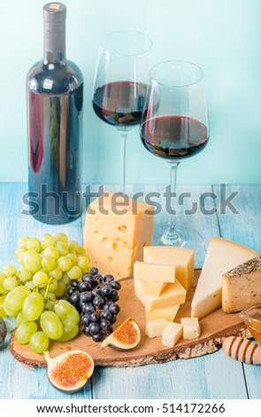 Grape, assorted cheese, figs and honey with red wine on blue wooden background.