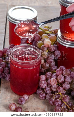 Grape jelly and bunches of red grapes - stock photo