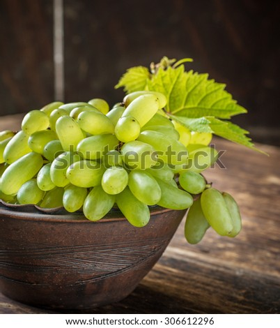 Grape varieties of ladies' fingers in a brown pottery bowl handmade on a dark wooden background with grape leaves. selective Focus - stock photo