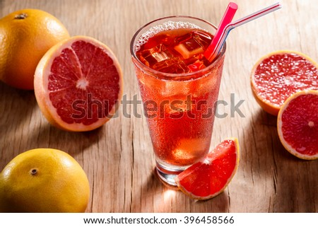 Grapefruit cocktail on the wooden table. Juicy citruses for a recipe. Colorful grapefruits were cut for a cocktail. - stock photo