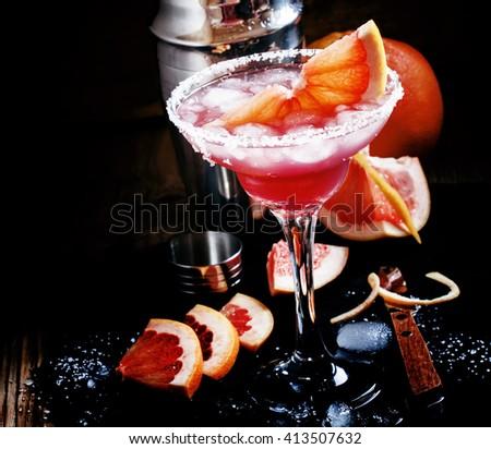 Grapefruit daiquiri with salt, metal shaker, black background, selective focus - stock photo