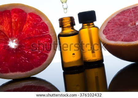 Grapefruit, essence, essential oil, extract, in amber glass bottle with dropper - stock photo